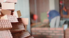 Stack of bricks at background of workers build wall unfocused Stock Footage