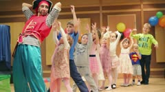 Adult girls in pirate suits play with kids which stand in column Stock Footage