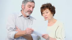 Serious senior couple hold paper list in hands and talk Stock Footage