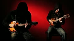 Duelling Mandolins - Two Mysterious Hooded Musicians Against Red Background HD Stock Footage