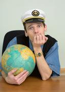 seaman misses on distant travel sitting at table with globe - stock photo
