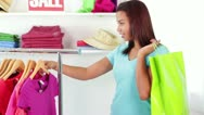 Attractive African-American Young Woman Trying Shirt with Shopping Bag Stock Footage