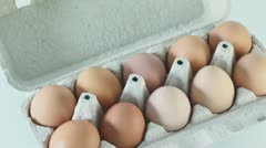 Ten brown eggs in cardboard  container circling closeup Stock Footage