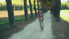 Young woman walking in the park, crane shot, slow motion Stock Footage