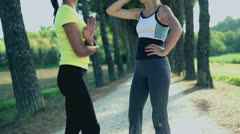 Two young girls after jogging in summer park, crane shot - stock footage