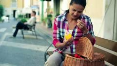 Young woman with basket full of shopping sitting on bench, steadicam shot Stock Footage