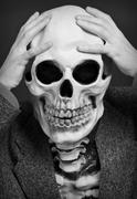 skeleton has clasped hands a skull - stock photo