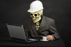 Comical man in helmet and skeleton mask with computer Stock Photos
