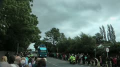 Olympic torch relay convoy on steep hill with large crowd Stock Footage
