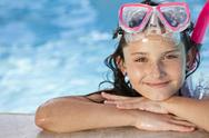 Stock Photo of happy girl child in swimming pool with goggles and snorkel