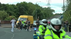 Flaming Olympic torch is carried round roundabout led by police motorbikes Stock Footage