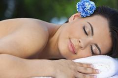 beautiful brunette woman relaxing at health spa with blue flower - stock photo