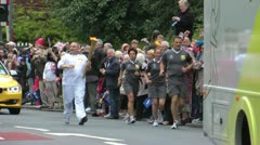 Runner with Olympic Flame passes large crowd - stock footage