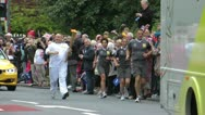 Stock Video Footage of Runner with Olympic Flame passes large crowd
