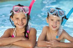 Boy and girl in swimming pool with goggles and snorkel Stock Photos