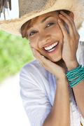 beautiful mixed race woman laughing in straw cowboy hat - stock photo
