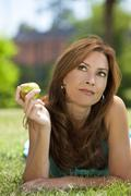 beautiful woman outside eating an apple and thinking - stock photo