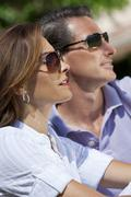attractive thirties couple in sunshine wearing sunglasses - stock photo