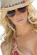 sexy blond girl in aviator sunglasses and straw cowboy hat - stock photo