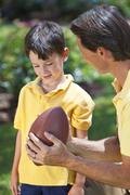 Father teaching his son to play american football Stock Photos