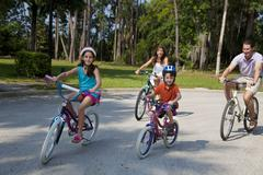 Modern family parents and children cycling Stock Photos