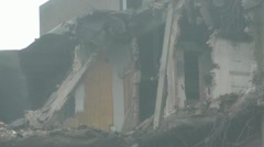 Pan across the exposed 7th floor of old tower block during demolition Stock Footage