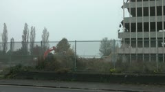 Old tower block undergoing demolition, digger works on rubble pile Stock Footage