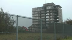 Wide shot of old tower block during demolition, digger works behind fence. - stock footage