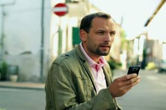 Man with cellphone texting message on the street, steadicam shot Stock Footage