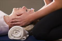 young therapist arranging crystals on female client for reiki therapy - stock photo