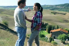 Young couple wathing at beautiful house in Tuscany, crane shot Stock Footage