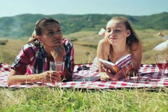 Portrait of two girlfriends drinking wine on picnic, crane shot Stock Footage