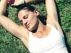 Top-view of young woman lying on the grass, crane shot Stock Footage