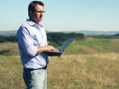 Young man with laptop looking at real-estate in Tuscany, crane shot Stock Footage