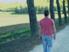 Young man walking in the park, crane shot, slow motion Stock Footage
