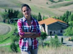Young woman in front of her beautiful house in Tuscany, crane shot - stock footage