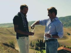 Male friends with wine enjoying panoramic view of Tuscany, crane shot Stock Footage