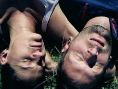 Top-view of young couple lying on the grass, crane shot Stock Footage