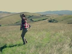 Young woman having fun on hill of Tuscany, slow motion, crane shot Stock Footage