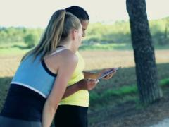 Young woman with personal trainer checking score on tablet computer, crane shot - stock footage