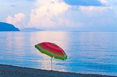 sunset and sunshade on beach - stock photo