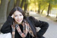 Smiling young woman in autumn park Stock Photos