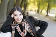 Stock Photo of smiling young woman in autumn park