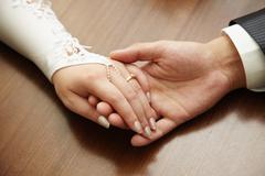 Hands of newly-married couple Stock Photos