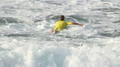 Surfer paddling heading out Stock Footage