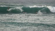 Surfers riding and catching a wave Stock Footage