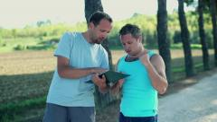 Young man with personal trainer discuss training plans in the park, crane shot Stock Footage