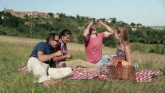 Group of happy friends playing cards on picnic Stock Footage