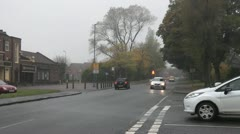 Cars turn at junction of tree lined road on misty autumn day - stock footage
