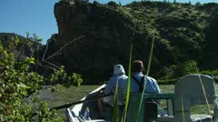 Guide and Angler by Bank with Crag in Background - stock footage